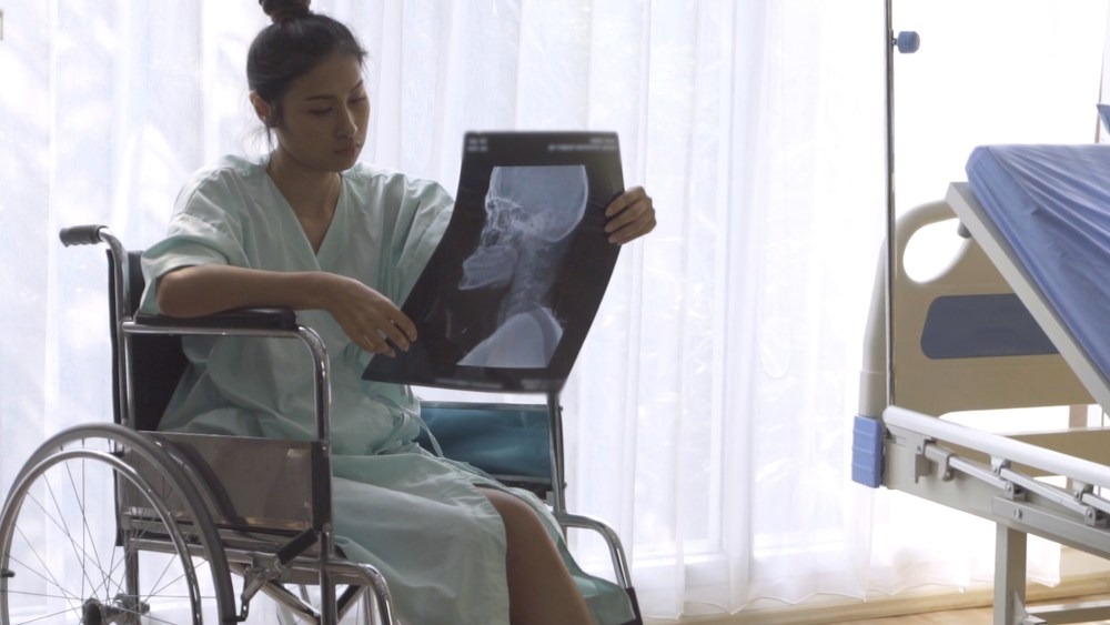patient in wheelchair looking at x-ray image
